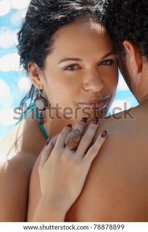 Honeymoon: happy young newlyweds smiling and relaxing near hotel pool. Vertical shape, head and shoulders - stock photo