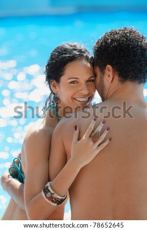 Honeymoon: happy young newlyweds smiling and relaxing near hotel pool. Vertical shape, waist up, copy space - stock photo