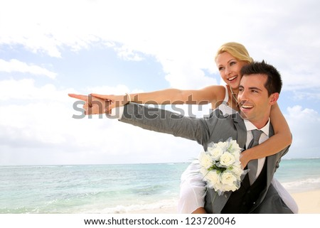 Honeymoon piggyback ride on the beach