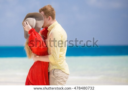 Honeymooners on the shore near by turquoise water of tropical beach.