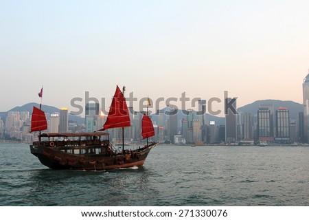 HONG KONG - APR 14, 2014: A traditional Junk boat in Victoria Harbor in Hong Kong, China. Victoria Harbour is a natural landform harbour situated between Hong Kong Island and Kowloon in Hong Kong. - stock photo