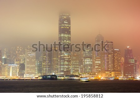 Hong Kong at foggy night with colorful city lights over sea with reflection.