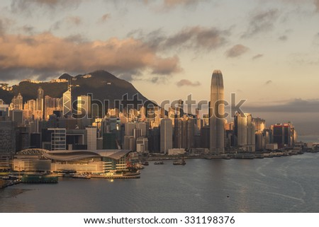 Hong Kong at Sunrise - The Rising Sun Lights Up Hong Kong Island with Victoria Peak and Wan Chai Ferry Terminal - stock photo