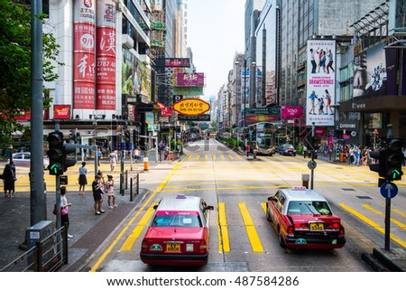 HONG KONG - AUGUST 8, 2016: City center with famous street view, car and bus traffic, numerous shops, cafes and restaurants. Downtown during the sunny day