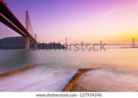 Hong Kong bridges at sunset over the ocean - stock photo