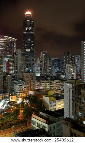 Hong Kong by night: different styles of buildings in Mong Kok district, from very modern skyscraper to low-rise. - stock photo