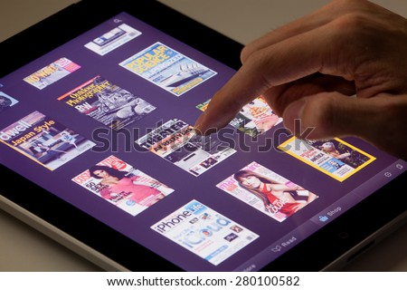 Hong Kong, China - August 7, 2011: Reading magazines on an iPad running the Zinio app. Zinio is a publishing technology and services company, which provides sales and distribution of printed material - stock photo