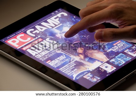 Hong Kong, China - August 7, 2011: Reading PC Gamer magazine on an iPad running the Zinio app. Zinio is a publishing technology and services company, which provides sales and distribution of printed - stock photo