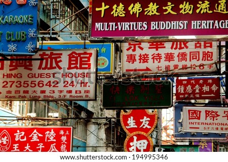 Hong Kong, China - December 17 2005:   A maze of commercial signs in both English and Chinese hang above a street in the busy Mong Kok district - stock photo