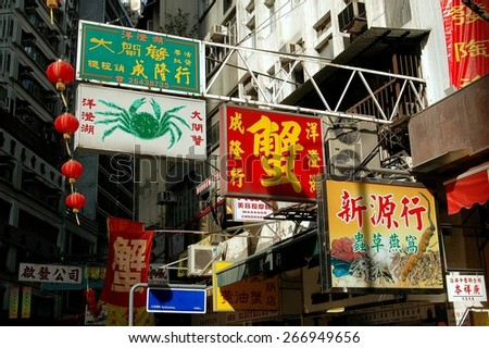 Hong Kong, China - December 15, 2005:  Restaurant and medicine shop signs hang from metal poles over Wing Lok Street in the Sheung Wan district