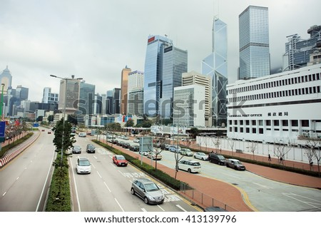 HONG KONG, CHINA - FEB 13: Broad street with skyscrapers and fast cornering car on February 13, 2016. Hong Kong dollar is the eighth most traded currency in the world. - stock photo