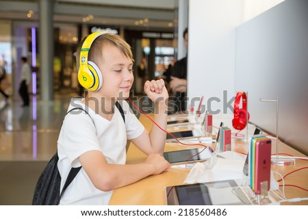 HONG KONG, CHINA - JUNE 18, 2014: The boy with headphones in Apple store in Hong Kong. Store is in a shopping center IFC Mall, it is very popular with locals and tourists visiting Hong Kong. - stock photo