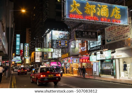 HONG KONG, CHINA - NOVEMBER 11, 2015: View of people, cars and neon signs in Tsim Sha Tsui, Kowloon, Hong Kong, China, at night.