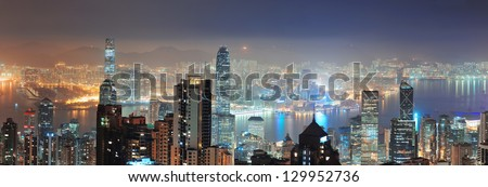 Hong Kong city skyline panorama at night with Victoria Harbor and skyscrapers illuminated by lights over water viewed from mountain top. - stock photo
