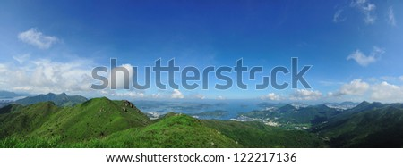 Hong Kong country side with hill, green plants, blue sky and sea. - stock photo