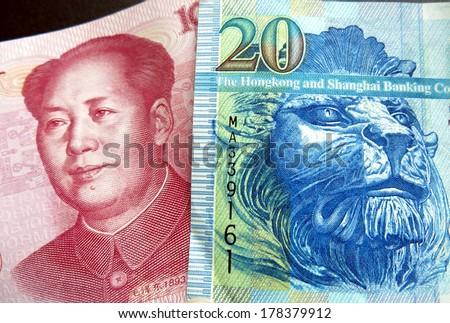 Hong Kong dollar juxtaposed against PRC Chinese Yuan - stock photo