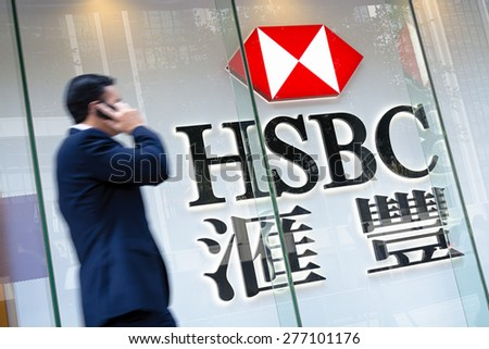 Hong Kong, Hong Kong SAR -November 17, 2014: Motion blured business man passing by an HSBC Bank sign in Hong Kong. HSBC Holdings plc  is the world's third largest bank by assets. - stock photo