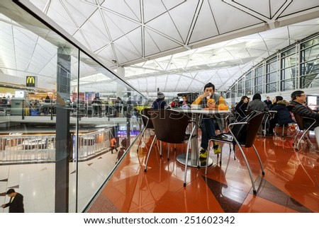 HONG KONG-JAN 12, 2015:Early morning travelers rest at Hong Kong's International Airport. As one of the world's largest and busiest passenger terminals, it served nearly 60 million travelers in 2013. - stock photo