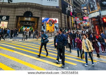 HONG KONG - JAN 16, 2015: Hong Kong cityscape view. People walking on crossroad at crowded streets with skyscrapers and shopping malls - stock photo
