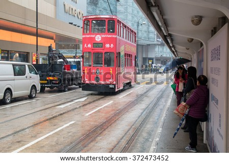 HONG KONG - January 28, 2016: Hong Kong cityscape view with double-deck electric tram moving on the street - stock photo