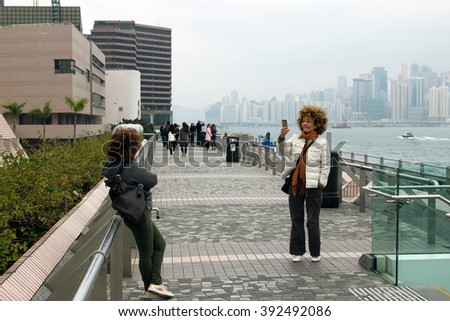HONG KONG - JANUARY 15,2016:Tourists take pictures and enjoy the famous Hong Kong island skyline across Victoria Harbour from the avenue of stars in Kowloon.