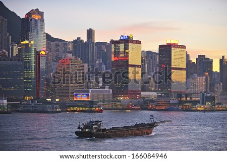 HONG KONG - JULY 04: Victoria Harbor on July 4, 2012 in Hong Kong. Big Cruise Ship departed from Ocean Terminal and drove across Victoria Harbor at sunset.