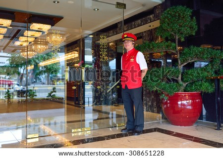HONG KONG - JUNE 02, 2015: hotel doorkeeper. Mandarin Oriental Hotel Group, a member of the Jardine Matheson Group, is an international hotel investment and management group with luxury hotels