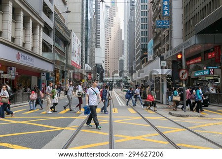 HONG KONG - MAR 29 : Tourists and locals walking across the street on Mar 29,2015 in HONG KONG