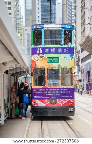 HONG KONG - MARCH 30: Passengers board an electric tram on Des Voeux Road in the downtown Central District Mar. 30, 2015. These historic streetcars have been in operation since 1904. - stock photo