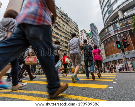 HONG KONG - MAY 18, 2014: People crossing a busy street in Causeway Bay. Hong Kong is one of the most densely populated areas in the world.  - stock photo