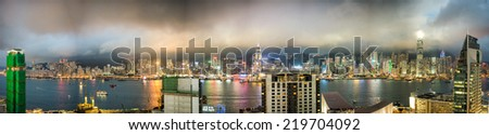 HONG KONG - MAY 12, 2014: Stunning panoramic night view of Hong Kong Island and Kowloon on a cloudy day from tower roof. Last year HK hosted more than 54 million visitors, most of them from mainland. - stock photo