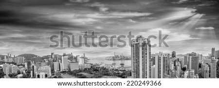 HONG KONG - MAY 12, 2014: Stunning panoramic view of Hong Kong Island and Kowloon on a cloudy day. Last year HK hosted more than 54 million visitors, most of them from the mainland. - stock photo