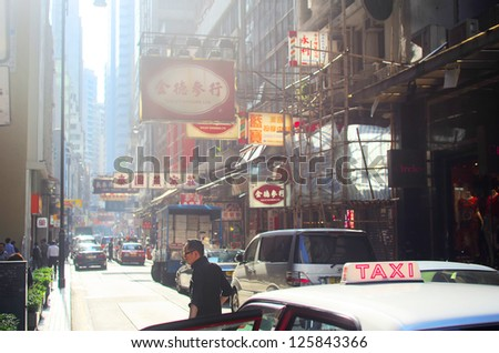 HONG KONG - MAY 22:  Sunny street on May 22, 2012 in Hong Kong. With a land mass of 1,104 km and population of 7 million people, Hong Kong is one of the most densely populated areas in the world - stock photo