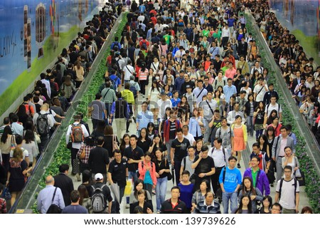 HONG KONG -MAY 13: The crowd of people in tunnel of Central MTR subway station on May 13 2013. 6 p.m. is the peak of rushing hour in central because all people come off work - stock photo