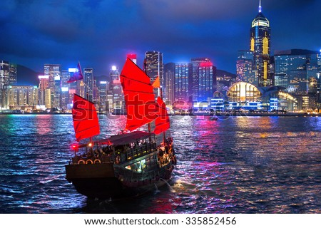 hong kong night view with junk ship on foreground - stock photo