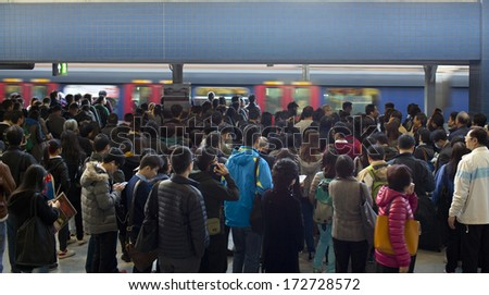 HONG KONG, NOVEMBER 29: crowd of passengers are waiting in Kowloon Tong station on 29 nov 2014. MTR is the main subway and train system in Hong Kong, and one of large transport networks in Asia - stock photo