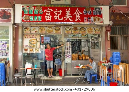 HONG KONG - November 6. Restaurant with Chinese characters for the dishes and a man who is eating food on an outdoor terrace on November 6, 2013 in Kowloon, Hong Kong. Owner is in the door opening.