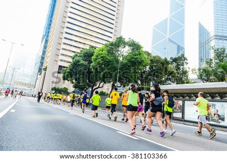 HONG KONG, OCT 2014: Group of asian runners on city during umbrella revolution - stock photo