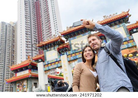 Hong Kong tourist attraction Wong Tai Sin Temple. Tourists taking selfie photo pictures by famous Hong Kong landmark. Romantic couple visiting and sightseeing Taoist temple. Asian woman, Caucasian man - stock photo