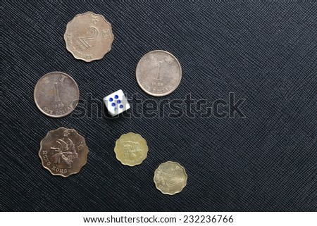 Hongkong dollar coin and dice put on the black color leather surface as a background represent the finance and gambling. - stock photo
