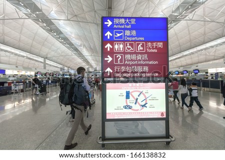 hongkong- NOVEMBER 11: A traveler views a departures board at Hong Kong airport on November 11, 2013 in Hong Kong, China. The Hong Kong airport handles more than 70 million passengers per year. - stock photo
