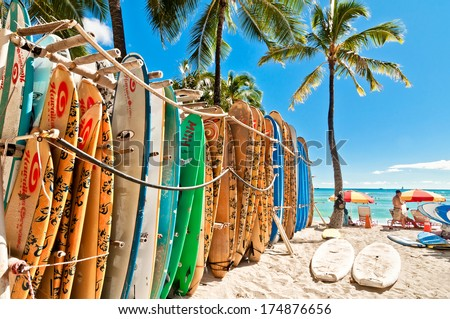 HONOLULU, HAWAII - SEPTEMBER 7, 2013: Surfboards lined up in the rack at famous Waikiki Beach in Honolulu. Oahu, Hawaii.  - stock photo
