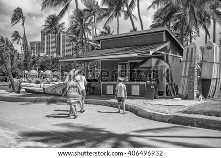 Honolulu, Hawaii, USA, April 16, 2016:  Afternoon view as a family of tourists checks out a Waikiki beach rental with surfboards and kayaks.