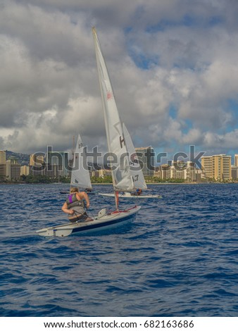 Honolulu, Hawaii, USA, July 22, 2017:  Young girl racing her sailboat offshore from Waikiki resorts during a sailing competition.