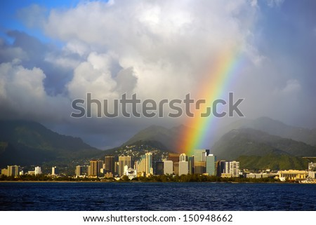 Honolulu Hawaii with a bright rainbow after a rain storm seen from the open ocean on Oahu island - stock photo