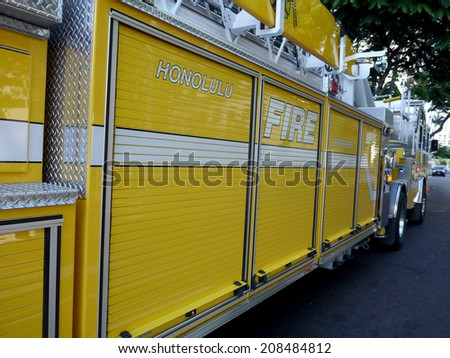 HONOLULU, HI - JULY 10, 2014: Side of yellow  Honolulu Fire Department Truck as it races down street to serve emergency situation. - stock photo
