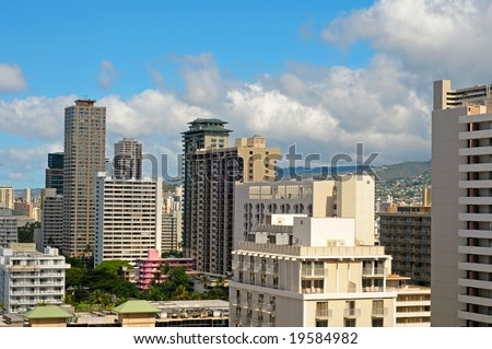 Honolulu hotels just off Waikiki Beach towering over a cute little pink hotel from a bygone era - stock photo