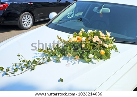 Hood of the wedding car decorated with a bouquet of flowers