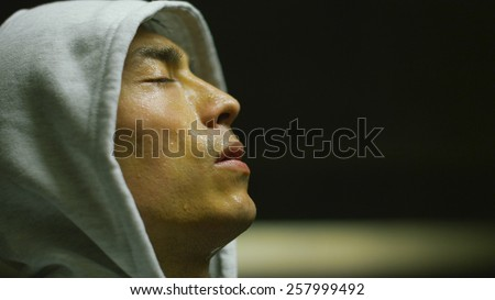 Hooded Asian man getting his breath back after an intense workout in urban environment - stock photo