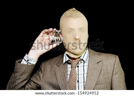 Hooded criminal in a business suit holding a glass to his ear as though listening and eavesdropping while stealing information or acting as a corporate spy in a white-collar crime - stock photo